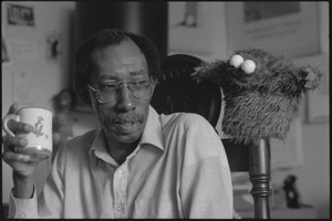 Thumbnail of Julius Lester at home: Lester seated, holding a mug, next to a Cookie Monster puppet