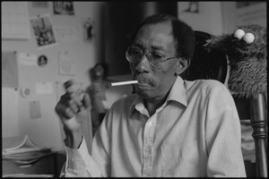 Thumbnail of Julius Lester at home: Lester lighting a cigarette, with Cookie Monster puppet