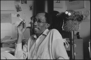 Thumbnail of Julius Lester at home: Lester seated with cigarette in hand, next to Cookie Monster puppet