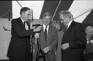 Thumbnail of Ceremonial groundbreaking for the Conte Center: Gov. William Weld receiving             ceremonial shovel from UMass Amherst Provost Richard O'Brien; unidentified man at far         left