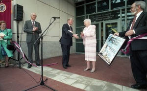 Thumbnail of Dedication ceremonies for the Conte Polymer Center: David K. Scott shaking hands             with Corinne Conte after the ribbon cutting, John Olver in background