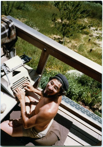 Mark Sommer, seated in full lotus, typing on front deck of Serendipity                      Farm, his self-reliant organic homestead in the coastal mountains of Northern California, 1984