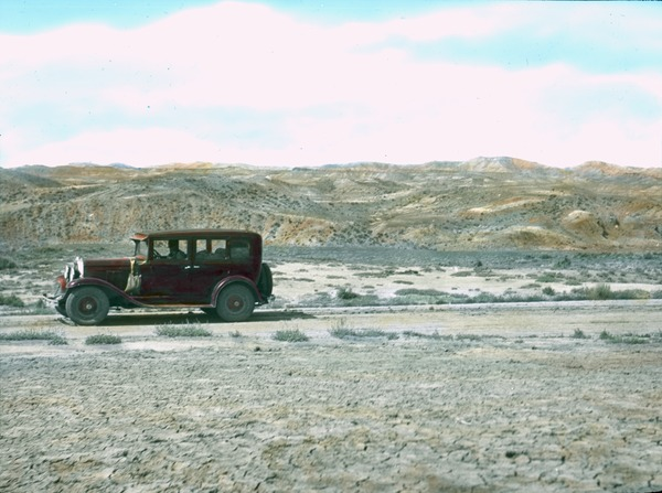 Old red automobile in the desert, ca. 1930