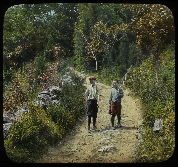 Going fishing, Mount Toby (two boys with branches walking on dirt path), ca. 1920