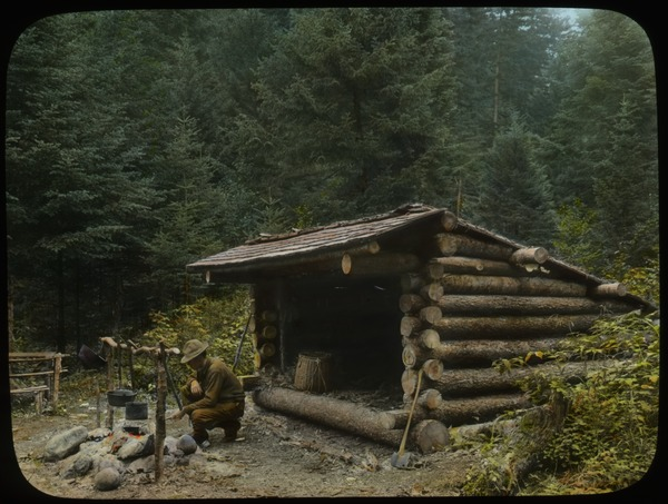 Man cooking over campfire in front of Adirondack log shelter, ca. 1920