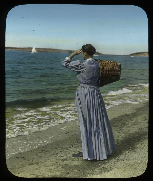 Woman with basket on beach scanning the horizon, ca. 1925