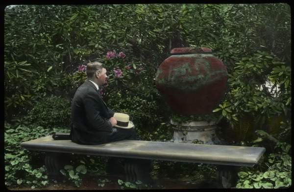 Cleveland (man sitting in garden, old terra cotta urn, stone bench, ferns, violets and rhododendrons), undated