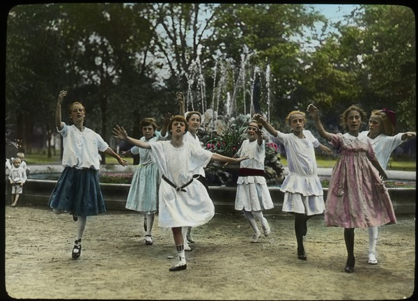 Girls dancing in park in front of water fountain, undated