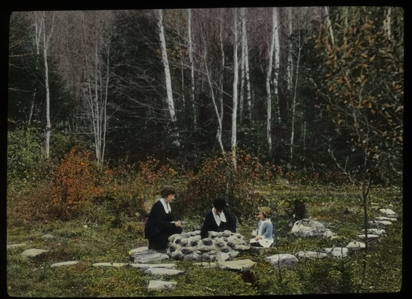 Two woman and child sitting around well (?) by birch forest, undated