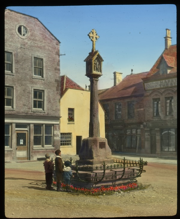 Stow-on-the-wold, Gloucestershire (town square with children looking up at religious monument), undated