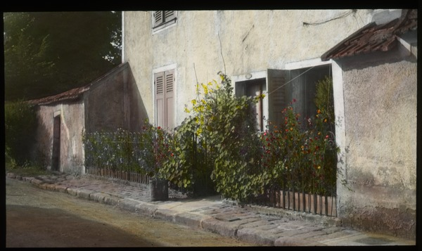 Garden in Fontainebleau (stucco house with flower plantings along street), undated