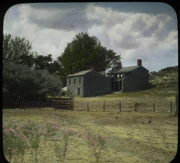 Old stone buildings by fenced- off field, undated