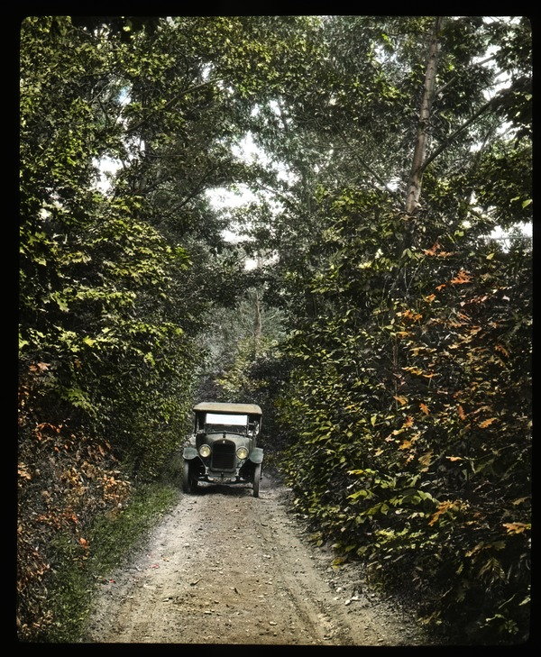 Automobile driving on a dirt road, ca. 1925