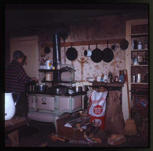 Nina Keller's mother cooking at the stove, Montague Farm Commune, January 1971