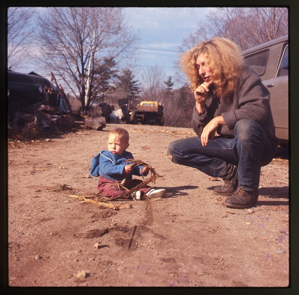 Charles and baby Eben crouched by a car (Scout) in front of the house at