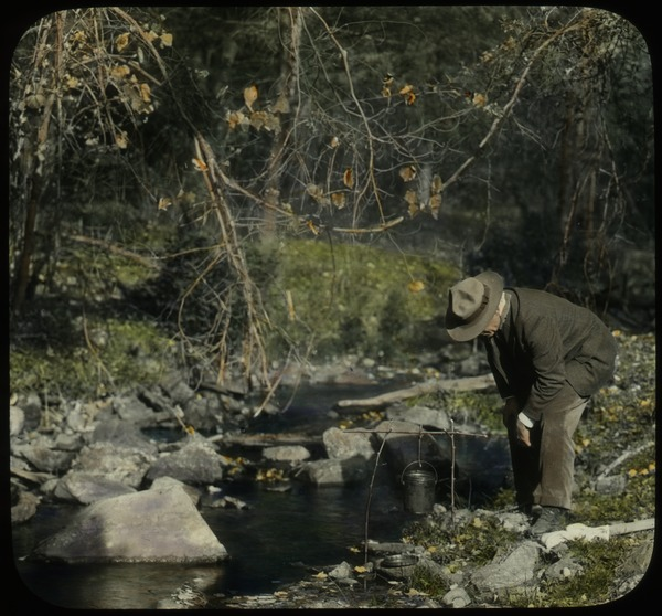 Orient Brook (man looking into pail, suspended by sticks beside brook), undated