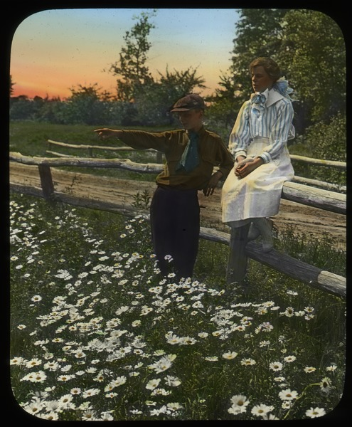 Boy and girl beside and on a wooden fence by road overlooking a field of ox eye daisies, undated