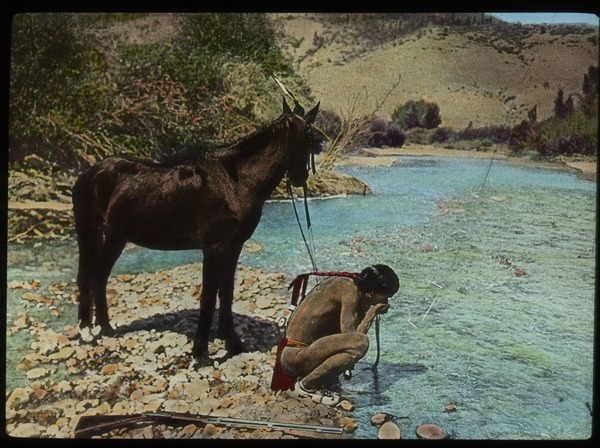 Arizona (Native American man drinking at stream, with horse and rifle), ca. 1918