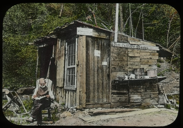 Old man reading outside of wooden hut, undated