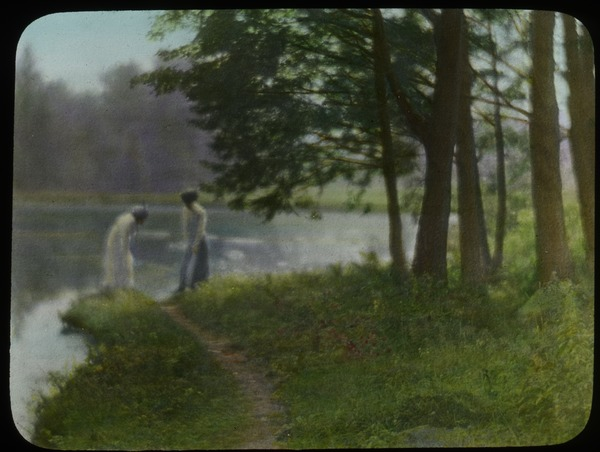Village park (two women at pond's edge), ca. 1920