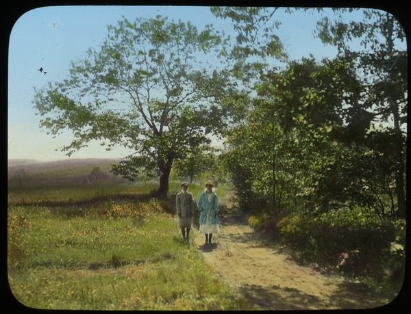 Man and woman on dirt road in meadow, ca. 1920