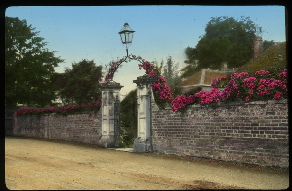 The Close, Salisbury, England (brick wall covered in pink flowers, decorative entrance archway with lamp), undated