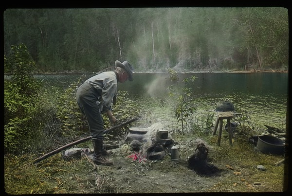 Lake Vassal, Quebec (man tending campfire by lake), undated