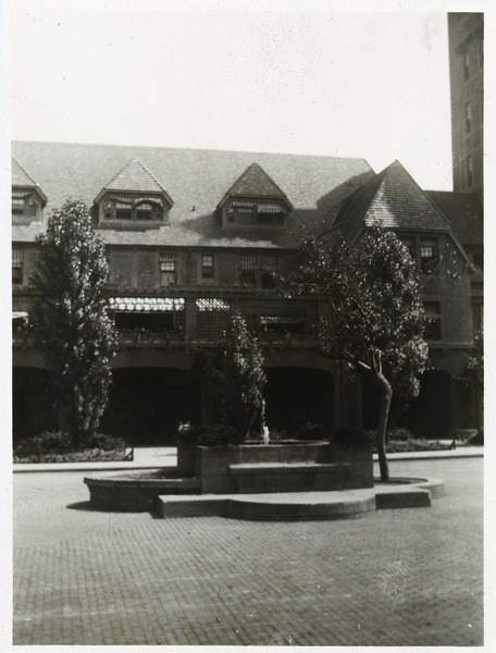 Brick-paved driveway and island with planters, ca. 1920