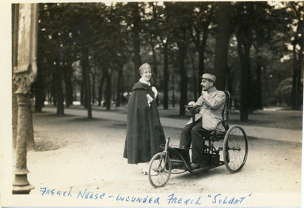 French nurse -- wounded French soldat: Nurse standing in a park with a disabled French soldier in a wheelchair: , ca. 1918