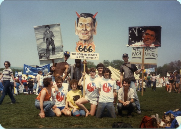 UMass Peacemakers contingent at the 'Four Days in April' demonstration in Washington D.C., holding image             of Ronald Reagan with devil's horns and caption '666 The bombing begins in five minutes', April 20, 1985