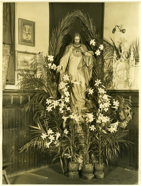 Chapel of the Comforter, Greenwich Village: Statue of Jesus of the Sacred Heart in a corner behind potted palms: , April 1926