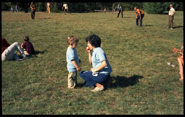 Woman and child at the picnic (man playing baseball in the background), Pine Beach: Rodney Hunt Company annual employee outing: , ca. 1970