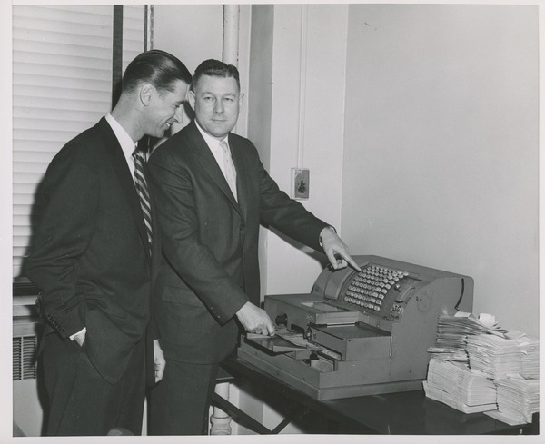 Two men looking at a cash register during an administrators' training event, ca. 1960