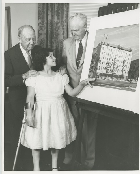 Jeremiah Milbank Sr. and Bruce Barton with a young ICD client in front of an illustration of prospective building plans, 1960?