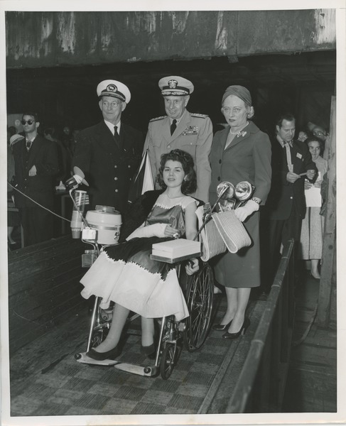 Young woman in wheelchair with others, 1958