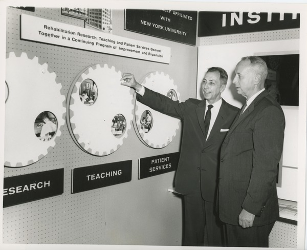 Two unidentified men in front of an ICD exhibit, July 18, 1961
