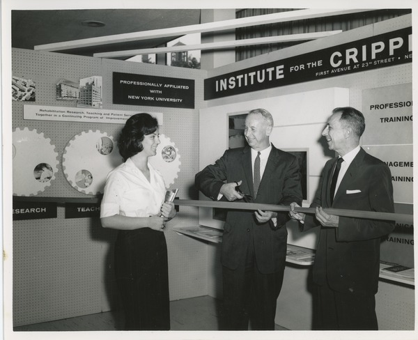 Two unidentified men cutting a ribbon next to an unidentified woman holding books in front of an ICD exhibit, July 18, 1961