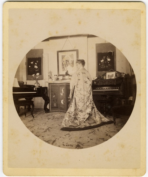 Abby F. Blanchard in the parlor, from behind, wearing a kimono, ca. 1890
