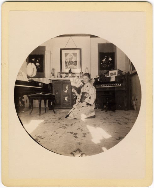 Abby F. Blanchard kneeling in the parlor, with fan and kimono, ca. 1890