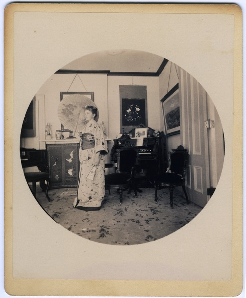 Abby F. Blanchard in the parlor, with parasol and kimono, ca. 1890