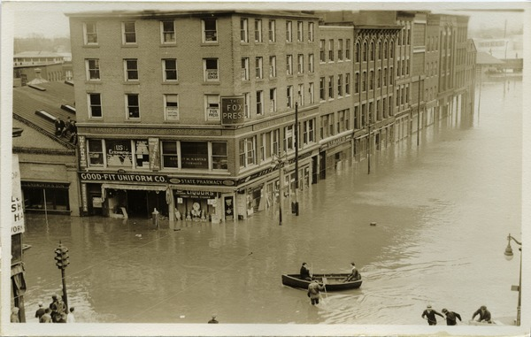 Aftermath of the great Hartford Flood: Flood waters on State Street (Manchester Leaf Tobacco Co. Building to City          Paper Co.) with row boat on the streets and men on roof: , ca. March 1936