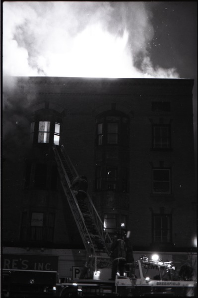 Fire on Main Street, Greenfield, Mass.: fire engine with ladder extended to burning building, December 27, 1972