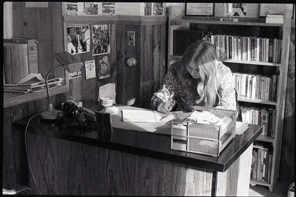 Lynn Smith seated at a desk in the Free Spirit Press office, ca. 1973