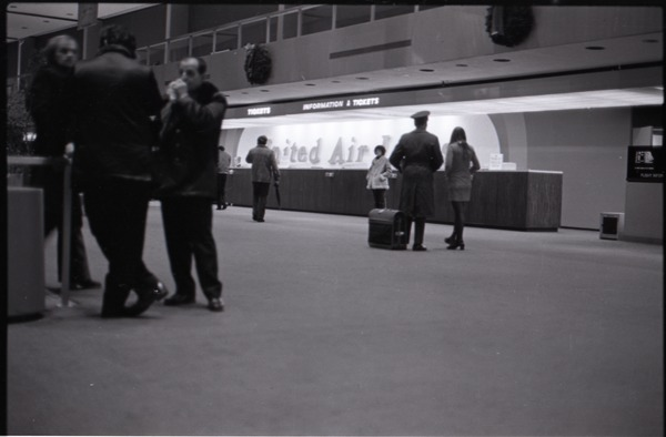 People milling about in front of United Airlines ticket counter at JFK airport, ca. December 13, 1972