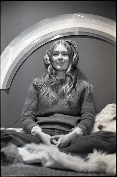 Lynn Smith on a faux fur blanket, modeling Koss headphones, ca. 1973