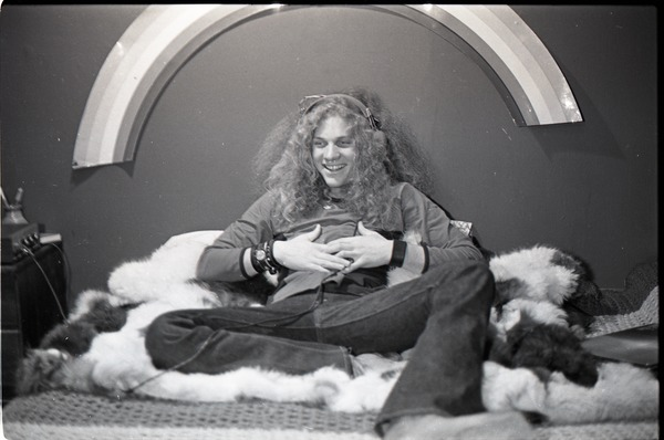 Richie Miller, lying on faux fur blanket, modeling Koss headphones, ca. 1973