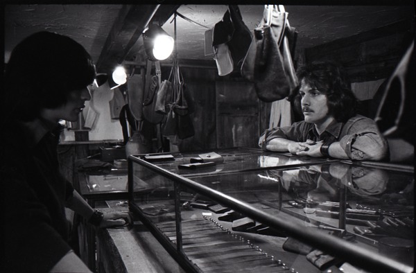 Don Muller with customer at the counter in the Leather Shed, ca. 1973