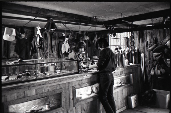 Don Muller behind the counter with a customer, the Leather Shed, ca. 1973