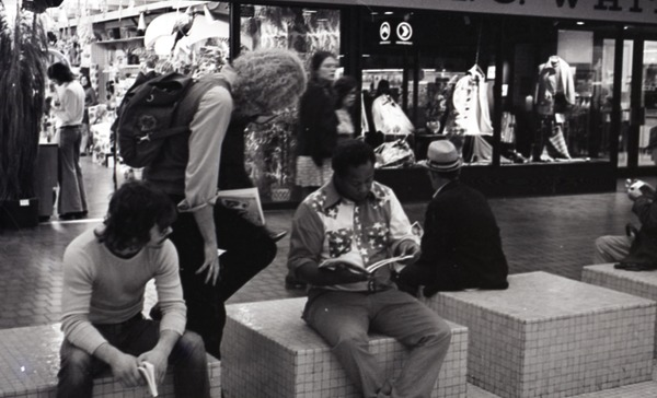 Commune member distributing Free Spirit Press in an indoor shopping mall:             communard looking over shoulder of African American man, ca. September 11, 1972