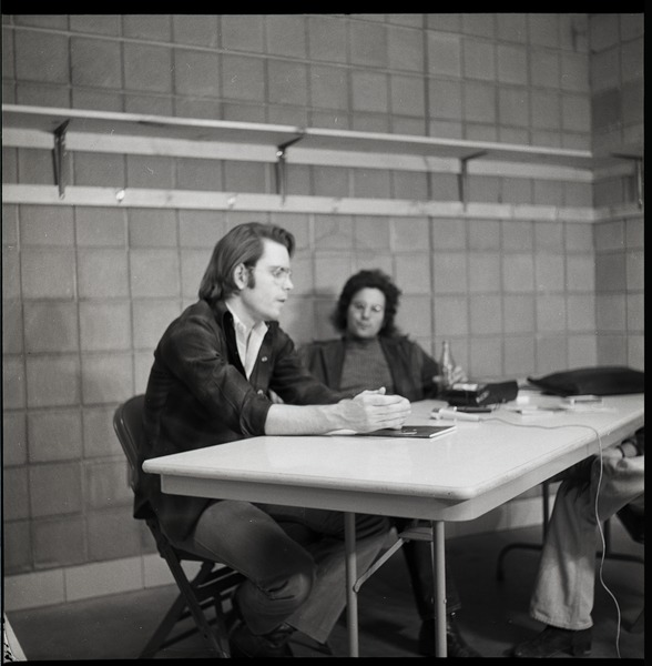 Bob Weir sitting at table with Mitch Sieser (l. to r.), ca. March 28, 1973
